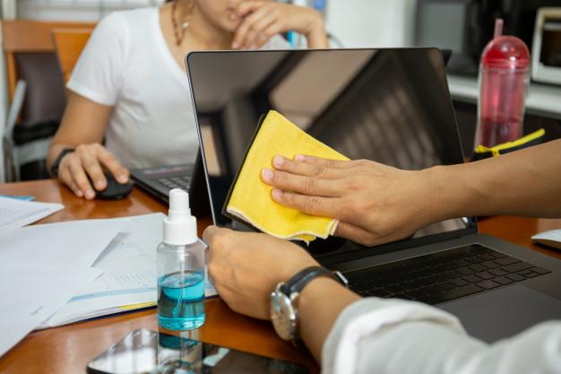 Homem limpando a tela do notebook com pano de microfibra